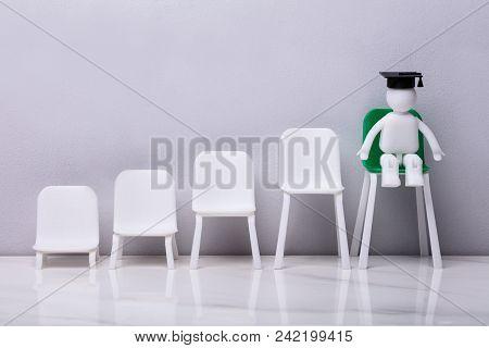 Miniature Figurine Sitting On Green High Chair Wearing Graduation Cap