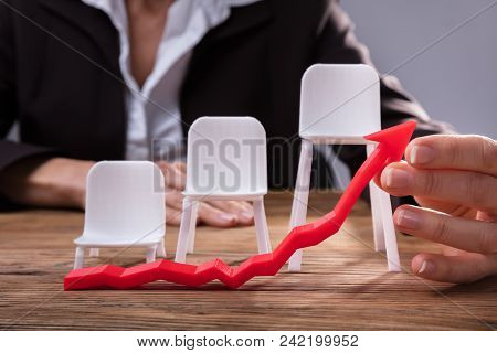Businessperson Holding Red Arrow Showing Upward Direction In Front Of Chairs On Wooden Desk