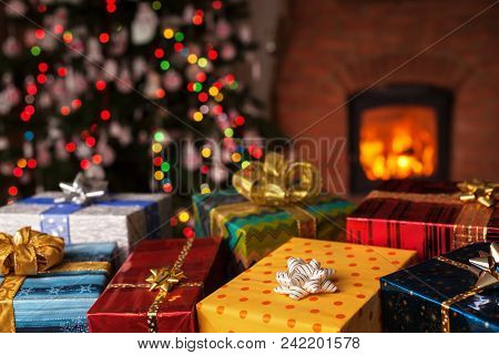 Many Christmas Presents In Front Of Xmas Tree And Fireplace In A Dark Room