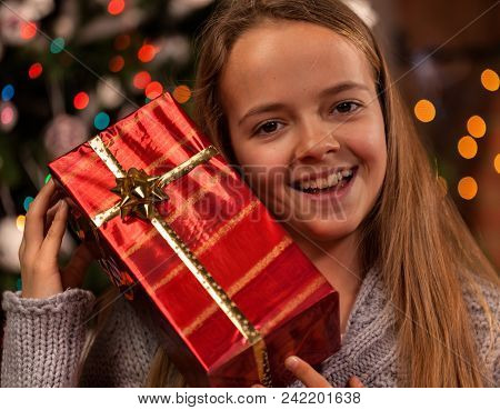 Happy Girl At Christmas Time With A Present Smiling And Holding Her Giftbox