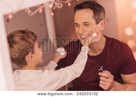 Happy Fatherhood. Cheerful Joyful Positive Man Looking At His Son And Smiling While Preparing For Sh