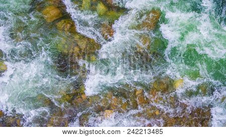 Top-down Drone View Of Rapids Of Mountain River With Wet Boulders On The Bottom