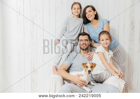 Portrait Of Happy Family Indoor. Handsome Father Holds Dog, Beautiful Brunette Mother And Two Daught