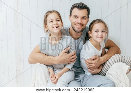 Father And Kids. Paternity Concept. Handsome Unshaven Affectionate Dad Embraces His Two Pretty Dauht