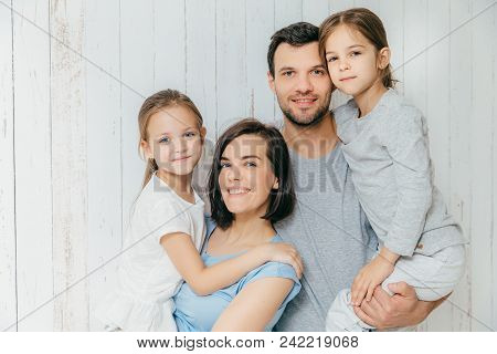 Good Looking Female And Male Parents Hold Their Beautiful Daughters, Spend Free Time All Together, E