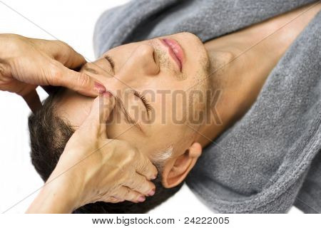 Mature man lying on his back, gets massage,reiki,acupressure on his face, focus on face and hands