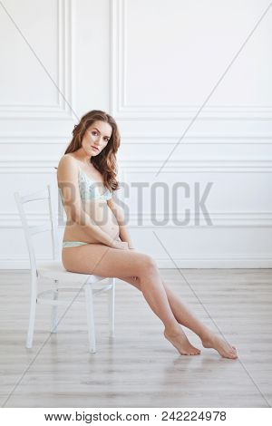 A Pregnant Woman In A Beautiful Light Underwear Sits On A White Chair. Empty Bright Room.