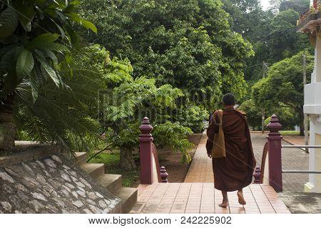 Thai Monk Walking Visit And Go To Respect Praying Buddha Statue At Wat Tham Khuha Sawan On October 4