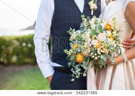Bride And Groom Hold Wedding Bouquet From Roses With Pink Ribbons And Stand On Background Of Sea, Be