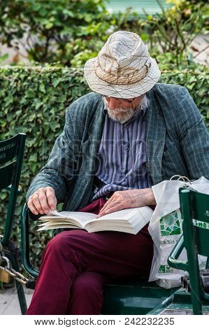 Paris, France - June 25, 2017: Old Elegant Man In A Hat Siting On A Chair Outside In The Inner Court