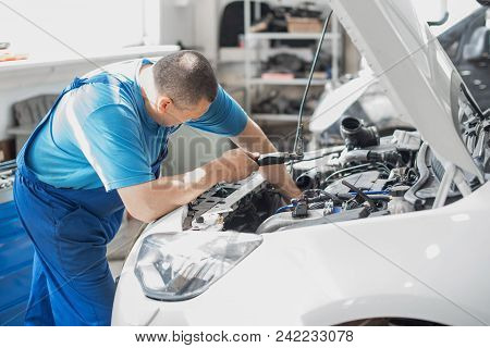 A Mechanic Working In A Car Workshop In A Blue Working Form Is Repairing A Gray Car. Auto Service.