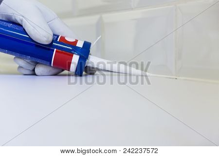Plumber Applying Silicone Sealant To The Countertop And Ceramic Tile. Home Improvement, Kitchen Reno