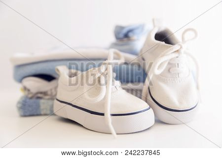 Set Of Things For A Newborn Baby Boy. Maternal Concept. Baby Clothes In Pile And Tiny Baby Shoes And