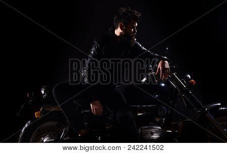 Man With Beard, Biker In Leather Jacket Lean On Motor Bike In Darkness, Black Background. Biker Cult