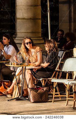 Paris, France - June 25, 2017: Parisians And Tourists Sit On The Terrace Of Le Nemours Cafe In The S