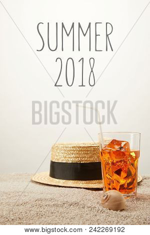 Close Up View Of Summer 2018 Lettering, Straw Hat And Refreshing Cocktail On Sand On Grey Backdrop