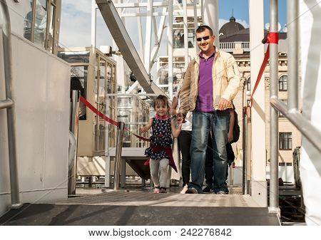 A Smiling Father With His Daughter Of Four Years Go Out Holding Hands, After Riding A Ferris Wheel.