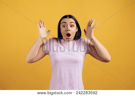 Portrait Of Surprised Young Girl In Pink Tshirt. Teen Emotions. Isolated On Yellow Background.