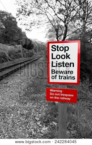 Railway Warning Sign In Black And White With Red Signpost Reading