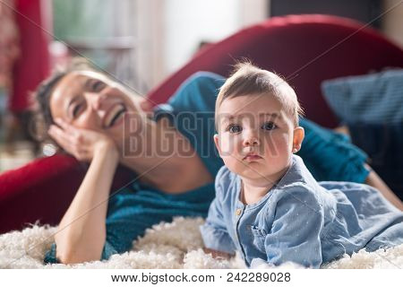 Mother Is Playing With Her Cheerful Baby On The Couch At Home