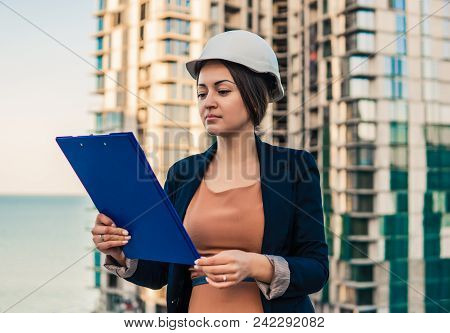 Beatiful Business Woman Engineer Is Standing With Plan Papers. Construction Project Is On Background