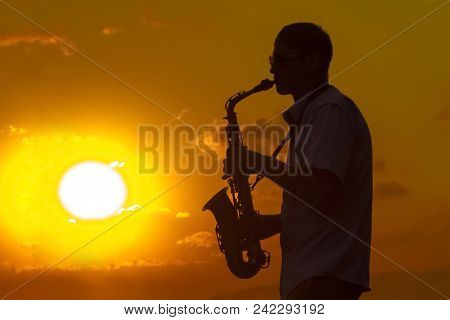 Silhouette Of A Young Musician At Sunset