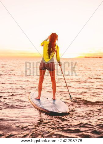 Attractive Sporty Woman Stand Up Paddle Surfing With Beautiful Sunset Or Sunrise Colors