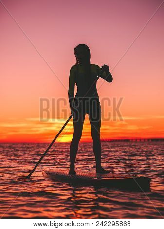 Sporty Woman Stand Up Paddle Boarding At Dusk On A Flat Warm Quiet Sea With Beautiful Sunset
