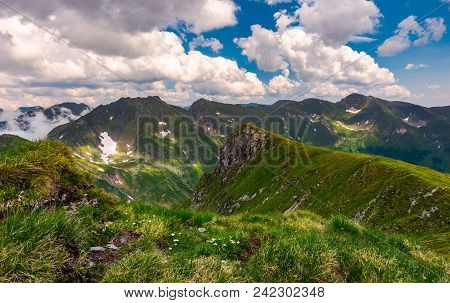 Grassy Hill On Rocky Cliffs Of Fagaras Mountains. Beautiful Summer Landscape Of Southern Carpathians