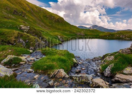 Rapid Streams Flow To Lake Capra In Mountains. Fagaras Mountain Ridge Under The Gorgeous Cloudscape