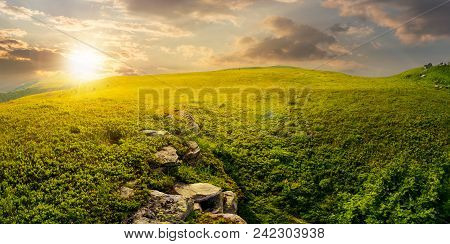 Panorama Of The Hillside Meadow At Sunset. Lovely Summer Landscape With Boulders Among The Grass. Lo