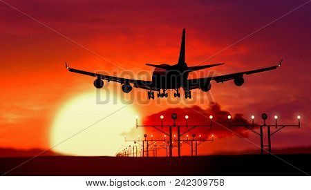Airplane Silhouette Of Jumbo Jet Lands At The Airport During Sunset. Shape Of Airplane And Flashing