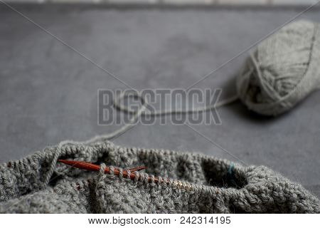 Gray Unfinished Sweater With A Ball Of Threads On A Gray Background Closeup.