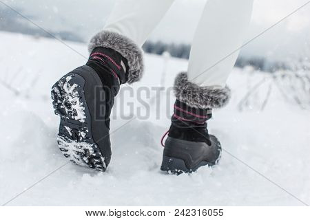 Detail on sole of black winter shoes with purple details, worn by girl walking in snowy country in winter. poster