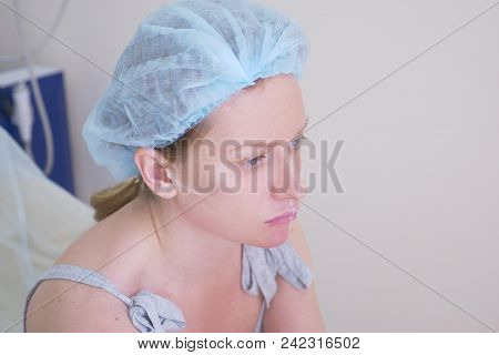 woman patient in a hygienic hat expects the procedure in the doctor's office. close-up. 4k. poster