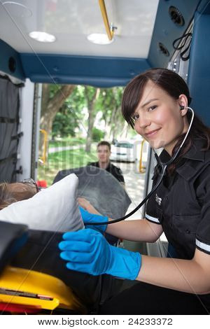 Portrait of EMT professional listening to heart rate of senior patient