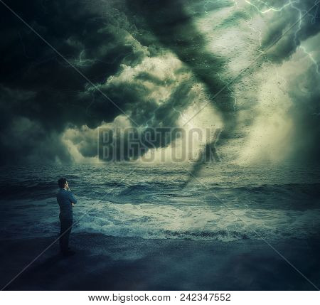 Thoughtful Brave Businessman Stand On The Shore In Fornt Of A Powerful Tornado Storm Over Sea Causin