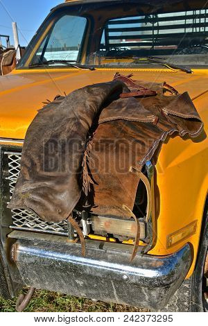 A pair of riding chaps for a cowboy are left on the hood of a pickup poster