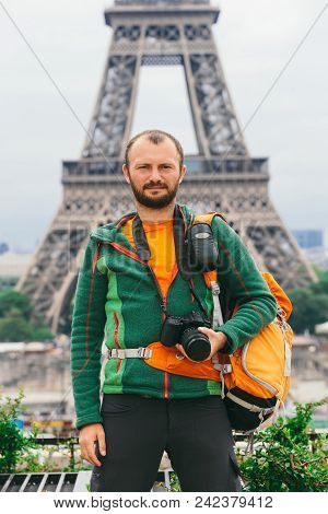 A Young Caucasian Caucasian Man With An Orange Backpack And A Photo Camera In His Hands Is Standing