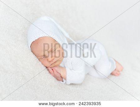Infant boy in white bodysuit
