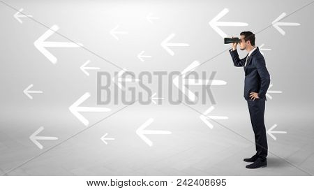 Young businessman standing and looking through binoculars with drawn arrows around