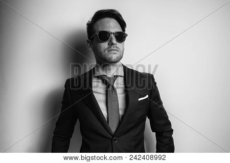 Black And White Portrait Of A Stylish Handsome Young Man Wear Suit And Sunglasses In Studio