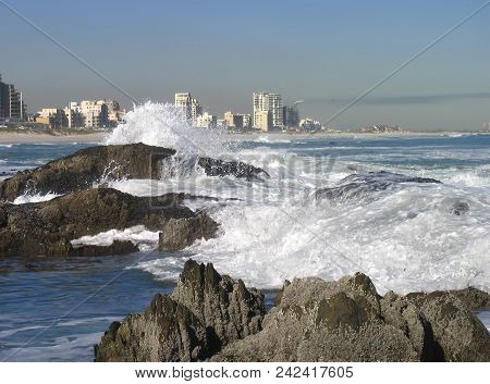 Waves Washing Of Some Rocks In The Fore Ground, With High Rise Buildings In The Back Ground 0007