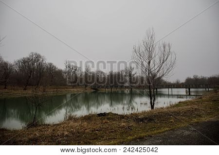 Amazing Landscape Of Bridge Reflect On Surface Water Of Lake, Fog Evaporate From Pond Make Romantic