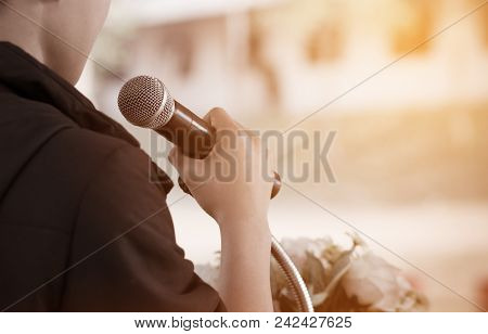 Microphone On Abstract Blurred Of Speech In Seminar Room Or Speaking Conference Hall Light; Computer