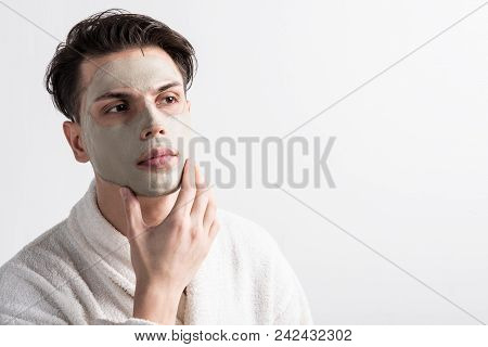 Good effect. Portrait of attractive guy in bathrobe is standing and touching his face with clay mask. He is enjoying anti-aging procedures and checking result of treatment. Copy space in right side poster