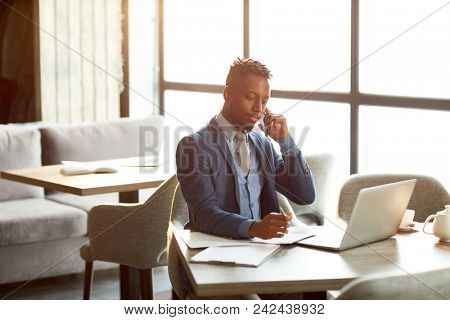 Young serious economist talking by smartphone, planning work and browsing in the net while sitting in cafe