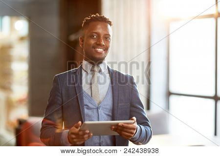 Successful and elegant businessman with touchpad spending working day in cafe