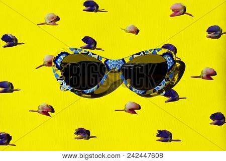 Travel, Vacation, Summer Concept. Blue Plastic Sunglasses Over Yellow. Top View Of Sunglasses And Fl