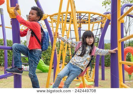 Two Kids Boy And Girl Having Fun To Play On Children's Climbing Toy At School Playground,back To Sch